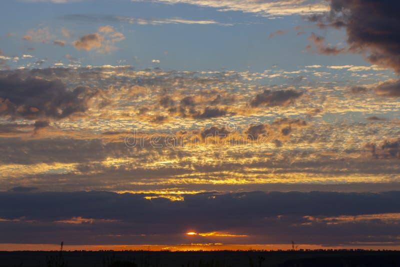 Mooie Zonsondergang De zonreeksen over de horizon draait donkere wolken in oranjegeel stock afbeelding
