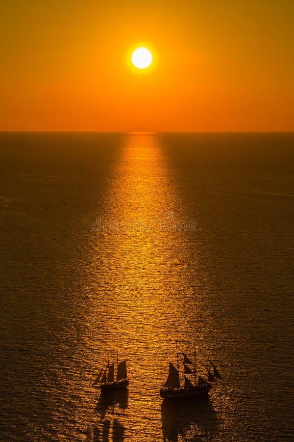 Mooie zonsondergang die over Santorini-caldera met twee boten, Oia, Santorini, Griekenland kruisen royalty-vrije stock fotografie