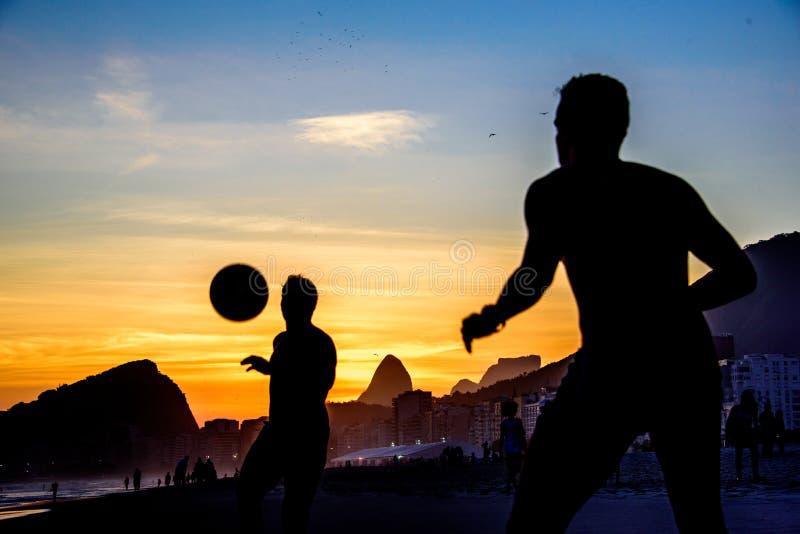 Mooie zonsondergang en silhouetten van mensen die de bal spelen in Copa royalty-vrije stock fotografie