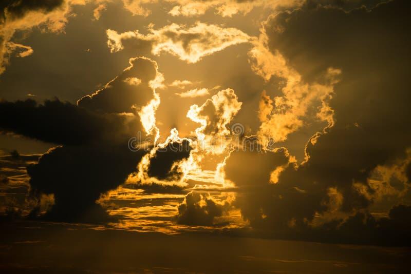 Mooie zonsondergang: het oranje licht van de zon door de wolken stock fotografie
