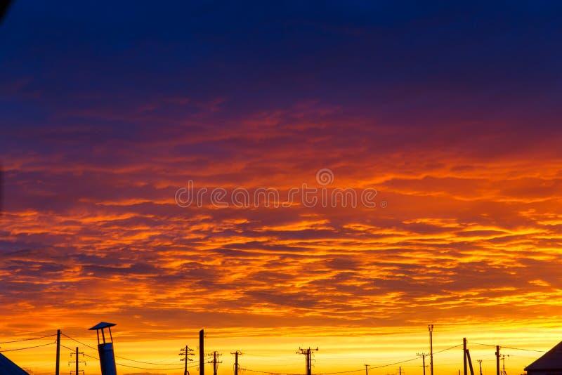 Mooie Zonsondergang Kleurrijke dramatische hemel bij zonsondergang Gelaagde regenwolken Heldere blauwe oranje achtergrond De text stock afbeelding