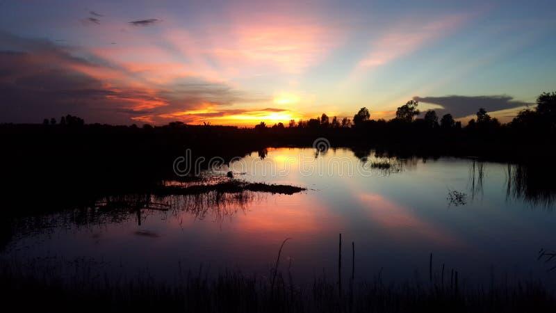 Mooie zonsondergang in lokaal dorp Thailand stock afbeelding