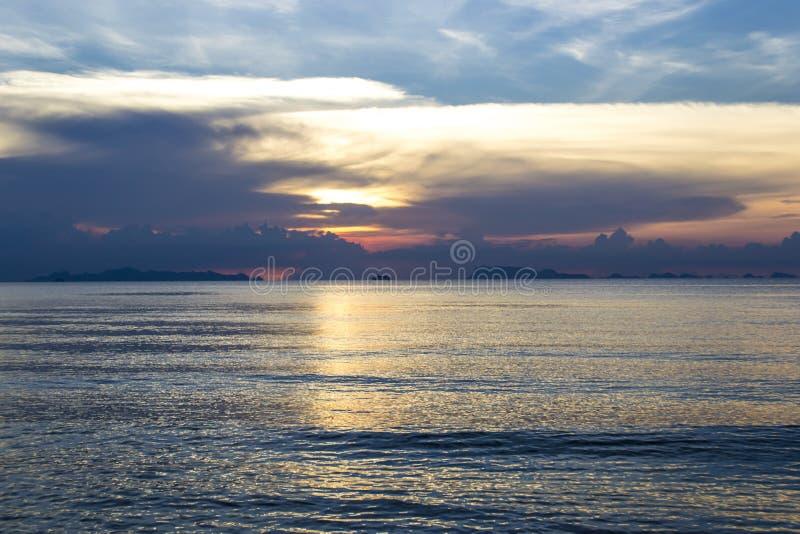 Mooie zonsondergang op het overzees Een stille overzees Veel wolken in de hemel avond De zonhuiden achter de wolken Blauwe hemel  stock foto