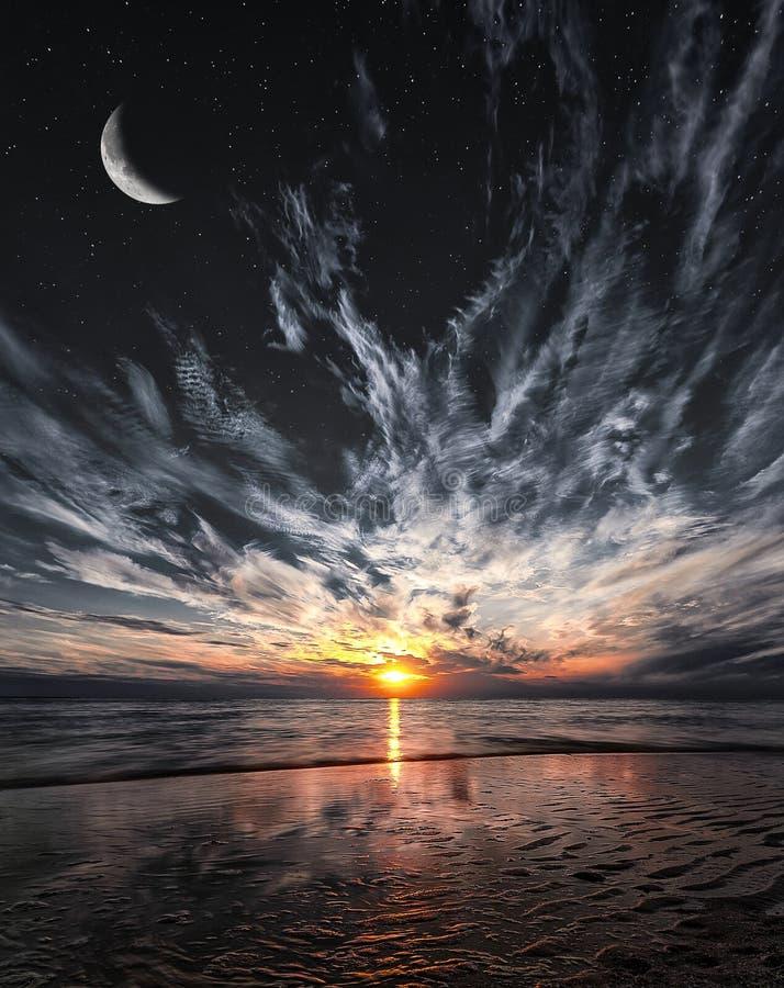 Mooie zonsondergang op het strand, de sterren en de maan op de hemel royalty-vrije stock fotografie