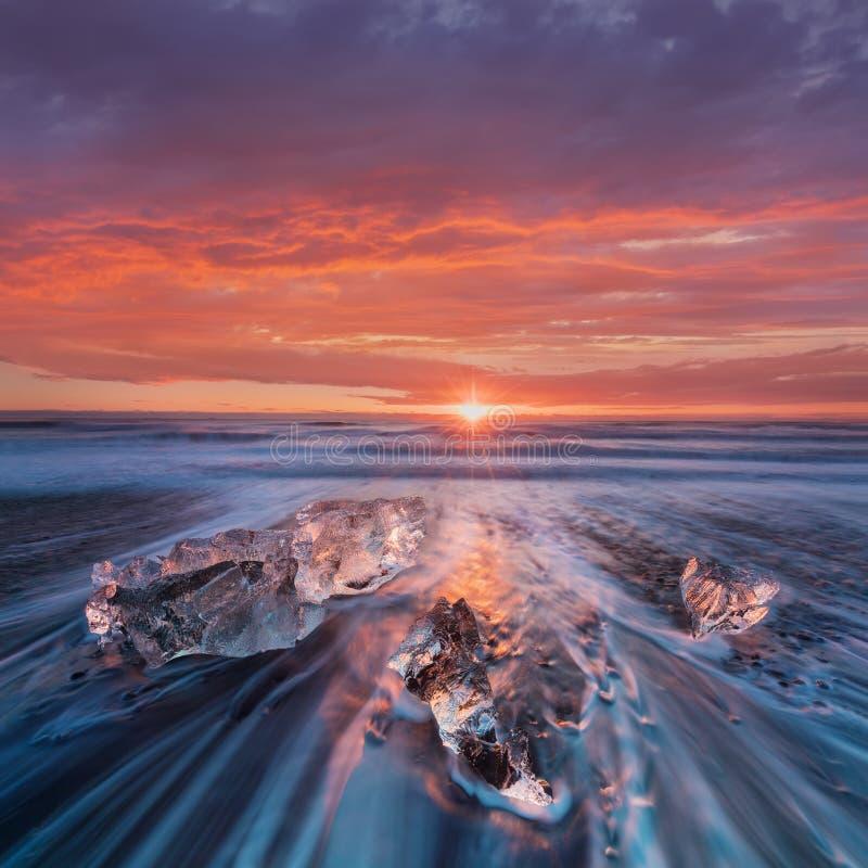 Mooie zonsondergang over beroemd Diamantstrand, IJsland Dit strand van de zandlava is volledig van vele reuzedieijsgemmen, dichtb stock fotografie