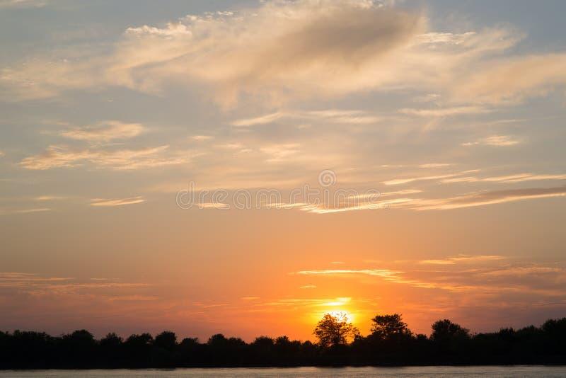 Mooie zonsondergang over de rivier met heldere wolken royalty-vrije stock afbeelding