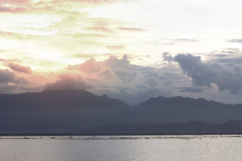 Mooie zonsondergang over kalm meer met bewolkte hemel en oranje sunli stock foto's