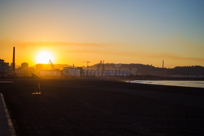 Mooie zonsondergang in Poniente-strand met het dok bij de achtergrond, in Gijon, Asturias, Spanje stock fotografie
