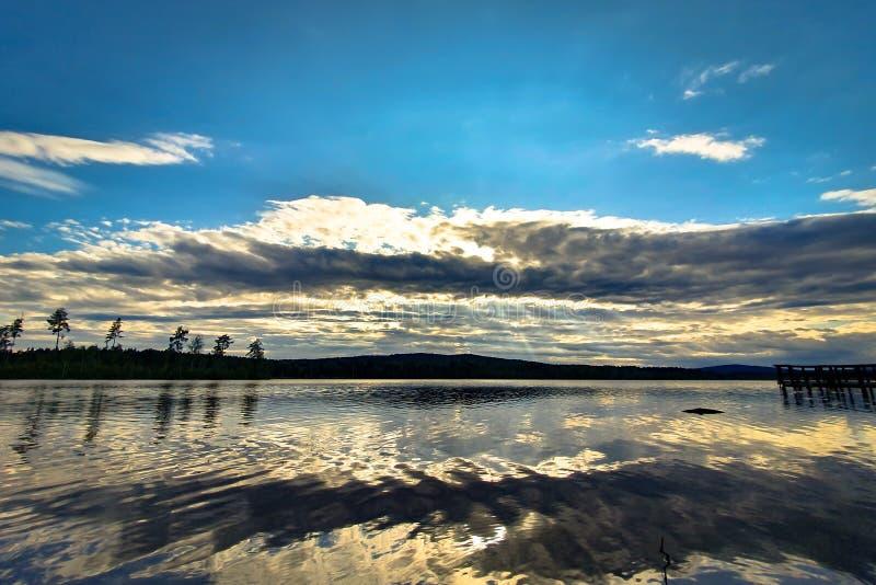 Mooie zonsondergang, weerspiegeld in kalm water Angersjon-meer tussen Hudiksvall en Soderhamn in Zweden royalty-vrije stock foto