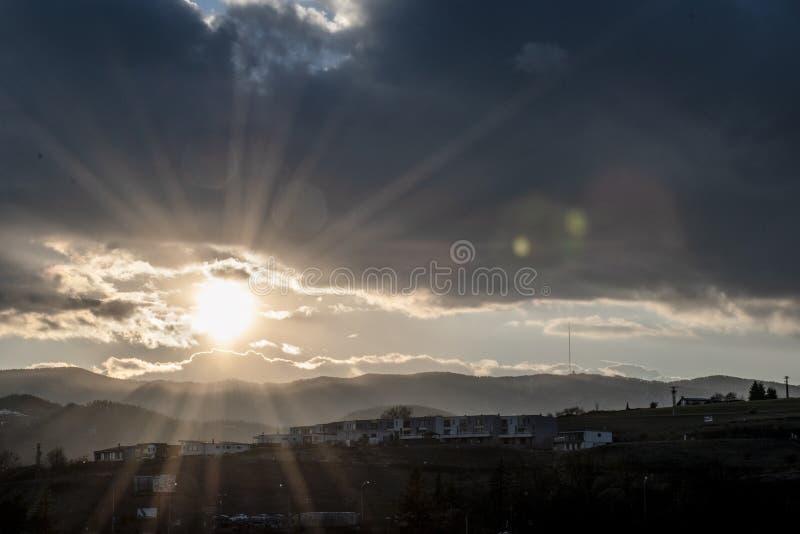 Mooie Zonsondergang Zon die achter bergen plaatsen Dramatische Wolken Dag aan nacht Verdonkerende hemel in de avond Stralen van L stock afbeelding