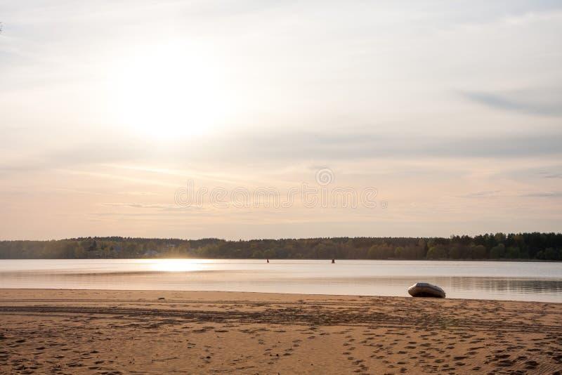 Mooie zonsonderganghemel door het strand met vastgelegde boot, Rusland - Volga stock foto's