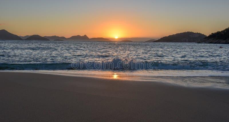 Mooie Zonsopgang met de zon die uit de oceaan, Rio de Janeiro toenemen stock afbeeldingen