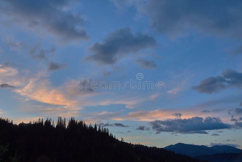 Mooie zonsopganghemel en wolken over het silhouet van een naaldbos royalty-vrije stock foto's