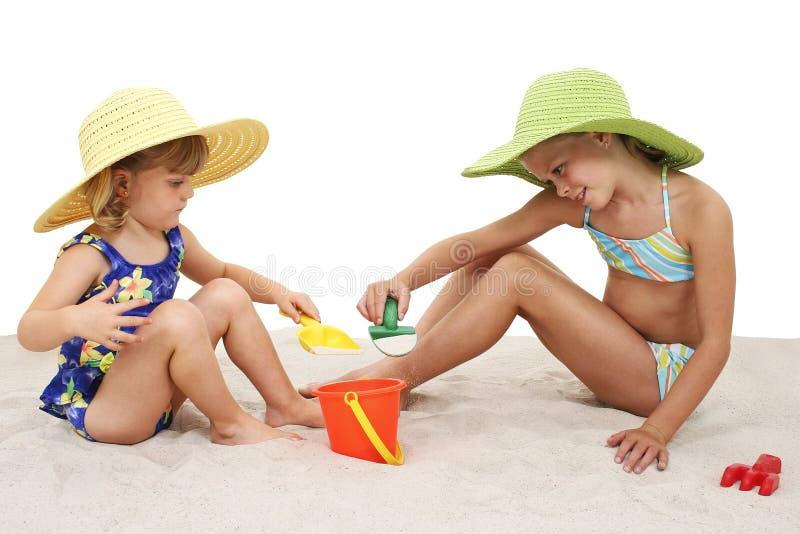 Mooie Zusters die in de Hoeden van het Strand in het Zand spelen royalty-vrije stock foto