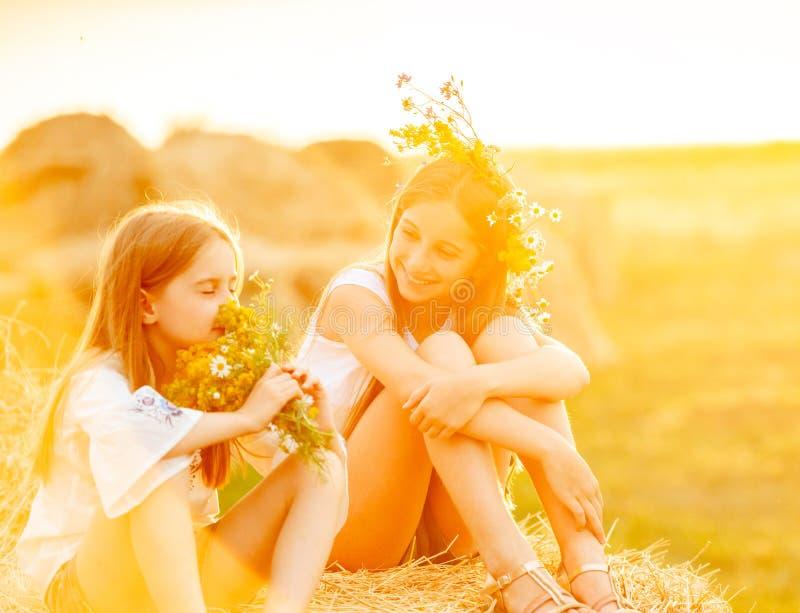 Mooie zusters die, op hooibergen glimlachen royalty-vrije stock afbeeldingen