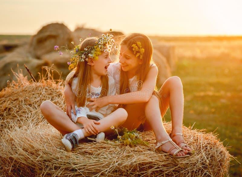 Mooie zusters die, op hooibergen glimlachen stock foto