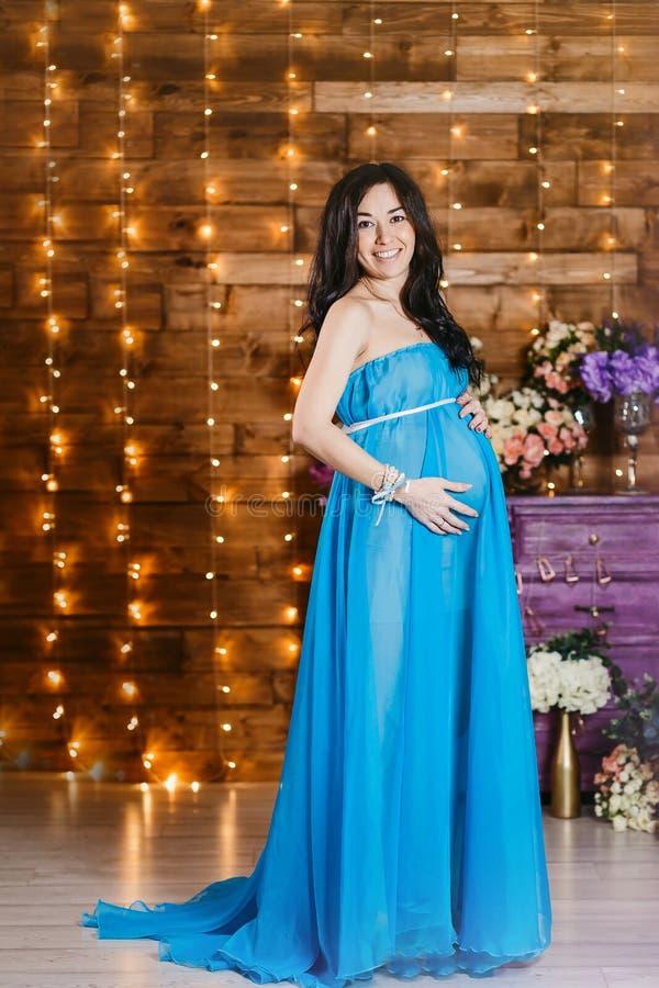 Mooie zwangere donkerbruine vrouw in lange zijde blauwe kleding stock foto