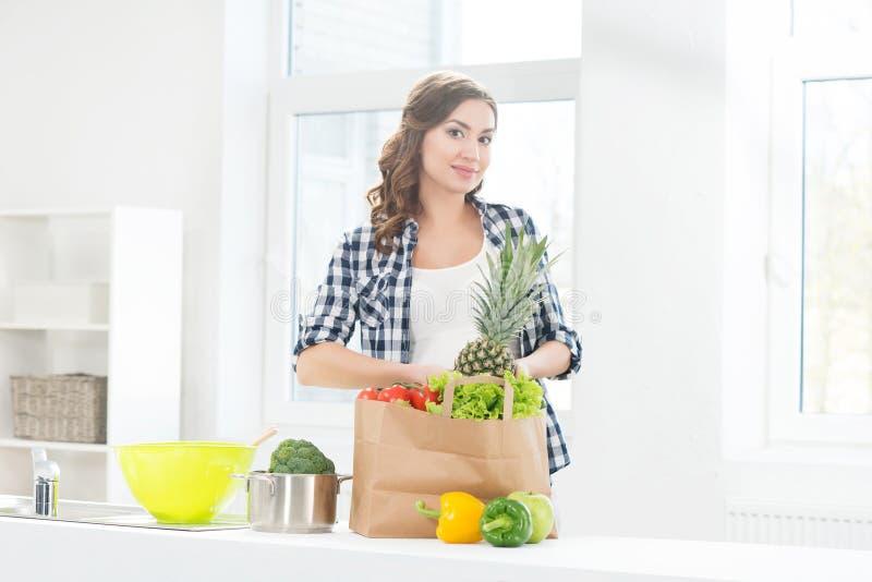 Mooie zwangere vrouw in de keuken met het winkelen zak en ananas stock foto