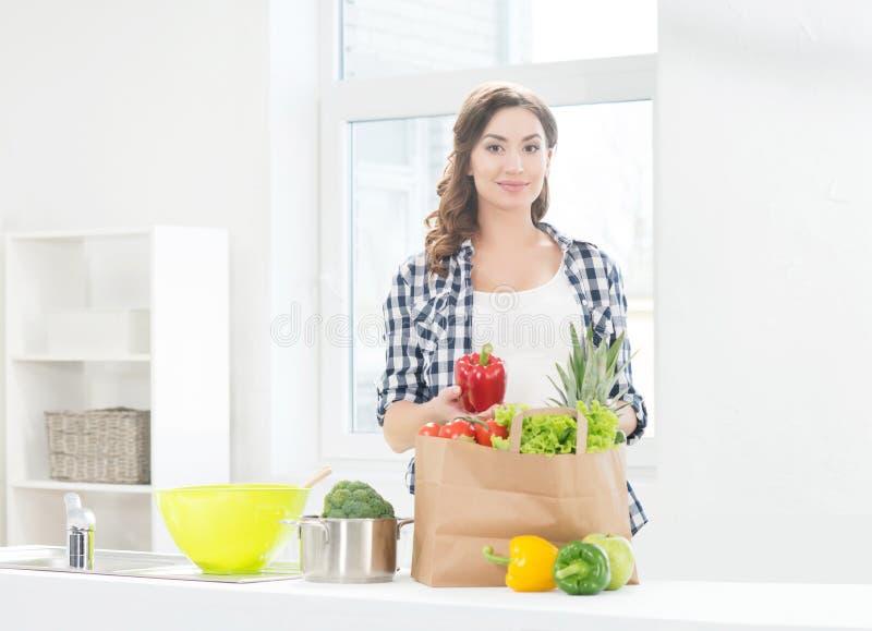 Mooie zwangere vrouw in de keuken met het winkelen zak en peper stock foto's