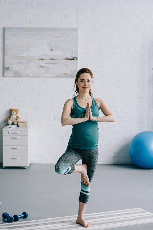 mooie zwangere vrouw die de positie van de yogaboom doen royalty-vrije stock fotografie