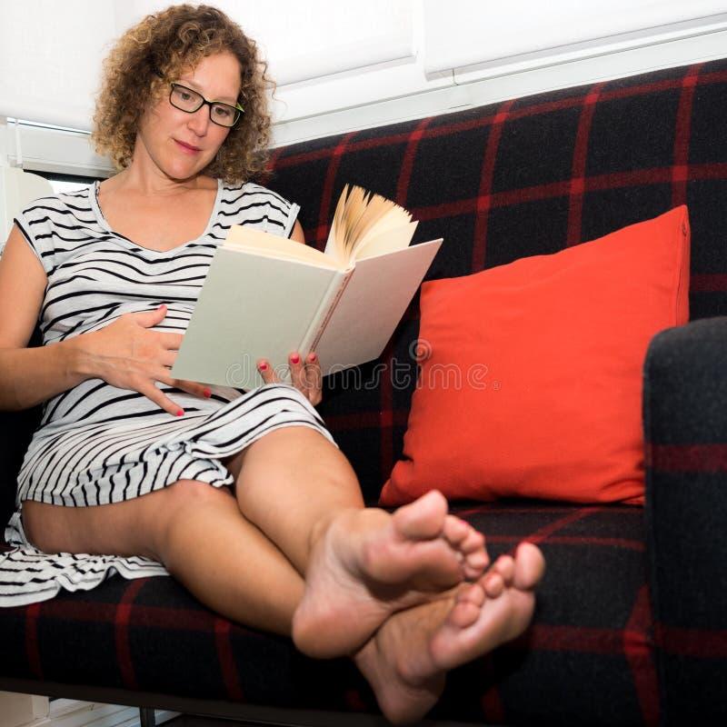Mooie zwangere vrouw die glazen dragen die op de laag zitten aangaande royalty-vrije stock afbeeldingen