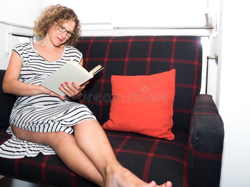 Mooie zwangere vrouw die glazen dragen die op de laag zitten aangaande royalty-vrije stock fotografie
