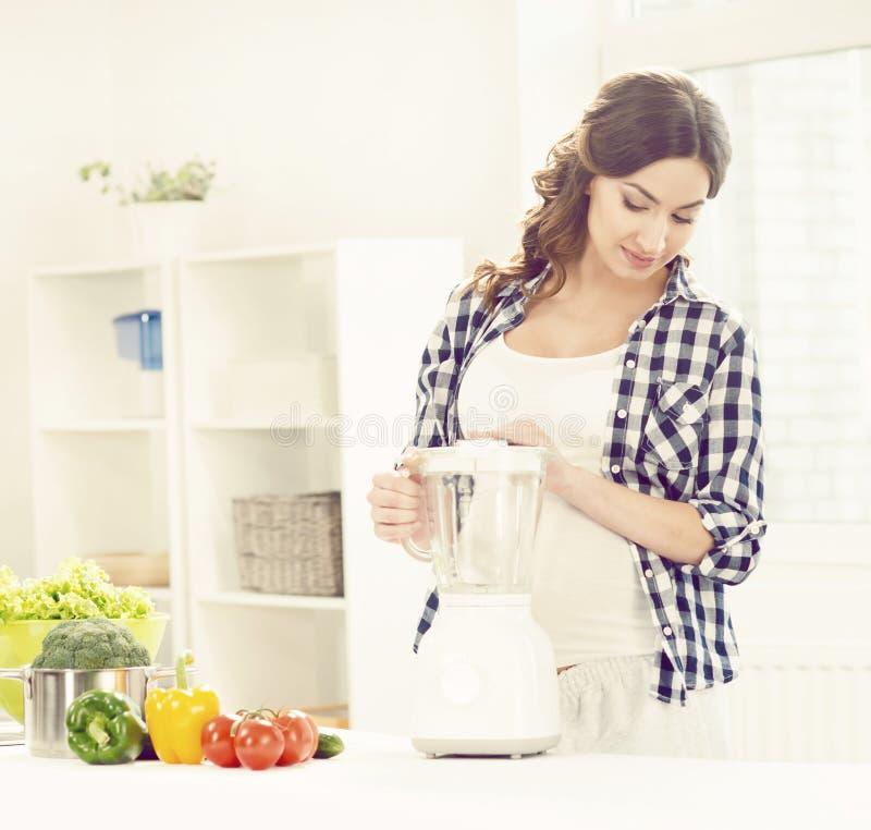 Mooie zwangere vrouw die ontbijt in keuken voorbereiden Motherh royalty-vrije stock afbeelding