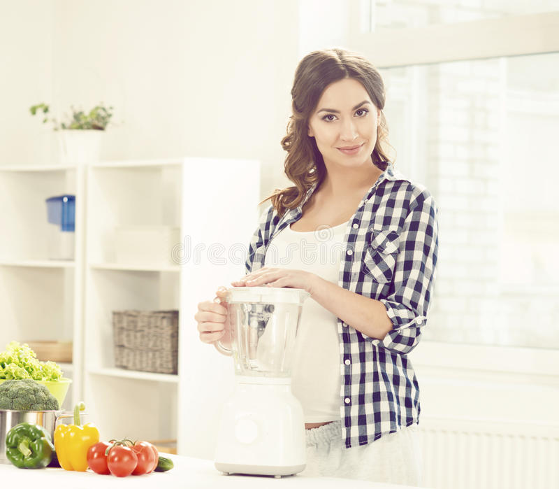 Mooie zwangere vrouw die ontbijt in keuken voorbereiden Motherh royalty-vrije stock afbeeldingen