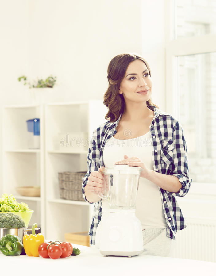 Mooie zwangere vrouw die ontbijt in keuken voorbereiden Motherh stock foto's