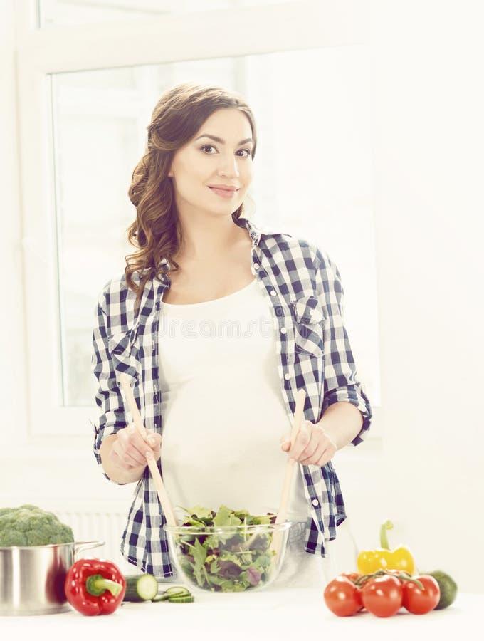 Mooie zwangere vrouw die ontbijt in keuken voorbereiden Motherh royalty-vrije stock foto's