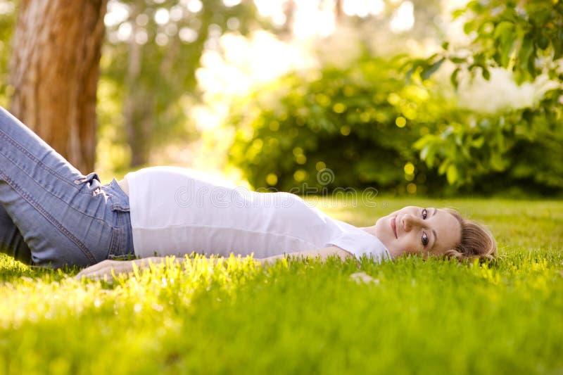Mooie zwangere vrouw die op het gras in zonnige dag liggen stock fotografie