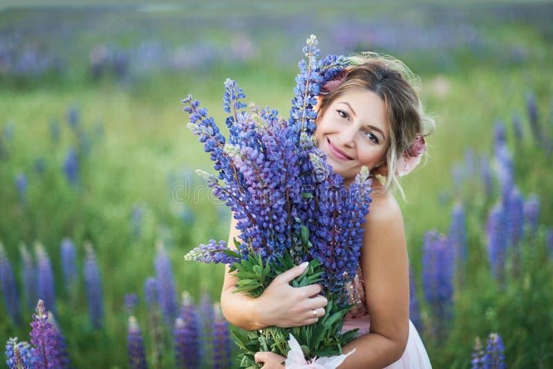 Mooie zwangere vrouw die in violette kleding een lupine houden bij zonsondergang op het gebied Het concept aard en Romaans stock afbeelding