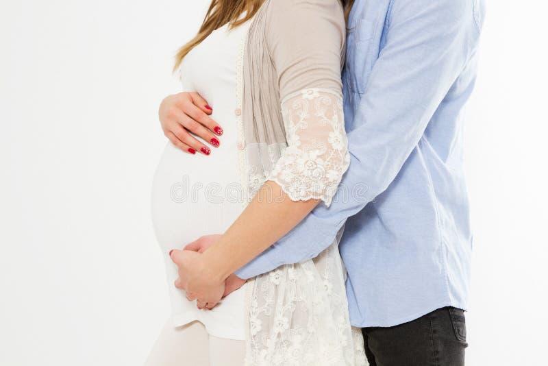 Mooie zwangere vrouw en haar knappe echtgenoot die die de buik, exemplaarruimte koesteren, op witte achtergrond, paar wordt geïso stock fotografie