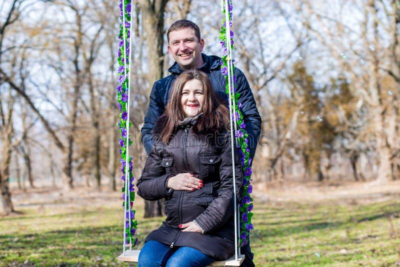 Mooie zwangere vrouw en haar knappe echtgenoot die de buik op de schommeling koesteren royalty-vrije stock foto
