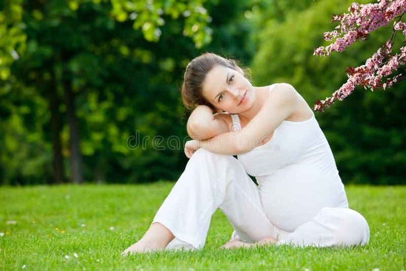 Mooie zwangere vrouw in het de lentepark royalty-vrije stock fotografie