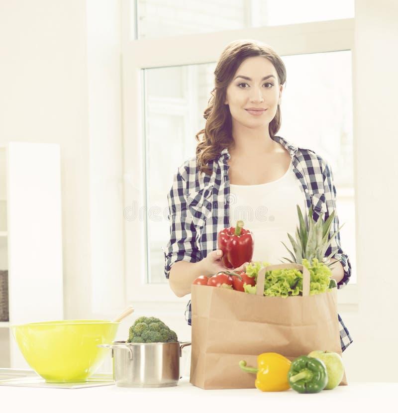 Mooie zwangere vrouw met het winkelen zakken in keuken Motherho stock afbeeldingen
