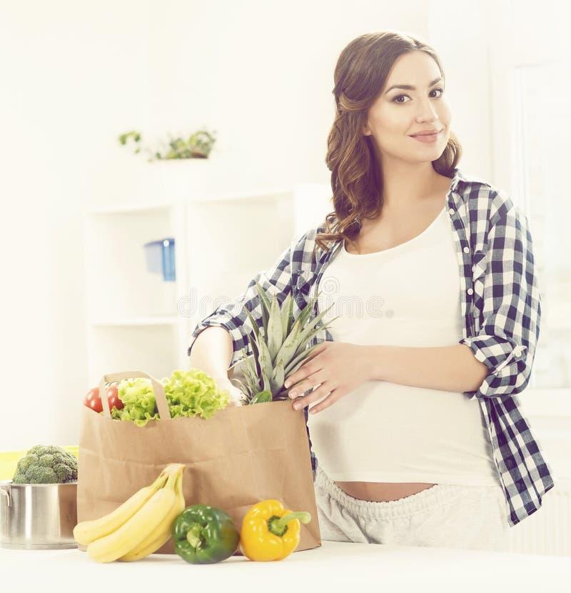 Mooie zwangere vrouw met het winkelen zakken in keuken Motherho stock foto's