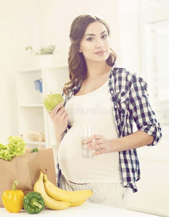 Mooie zwangere vrouw met het winkelen zakken in keuken Motherho royalty-vrije stock foto's