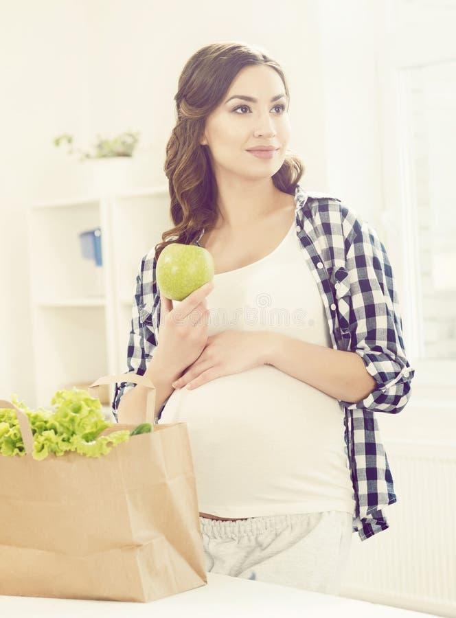 Mooie zwangere vrouw met het winkelen zakken in keuken Motherho stock afbeelding