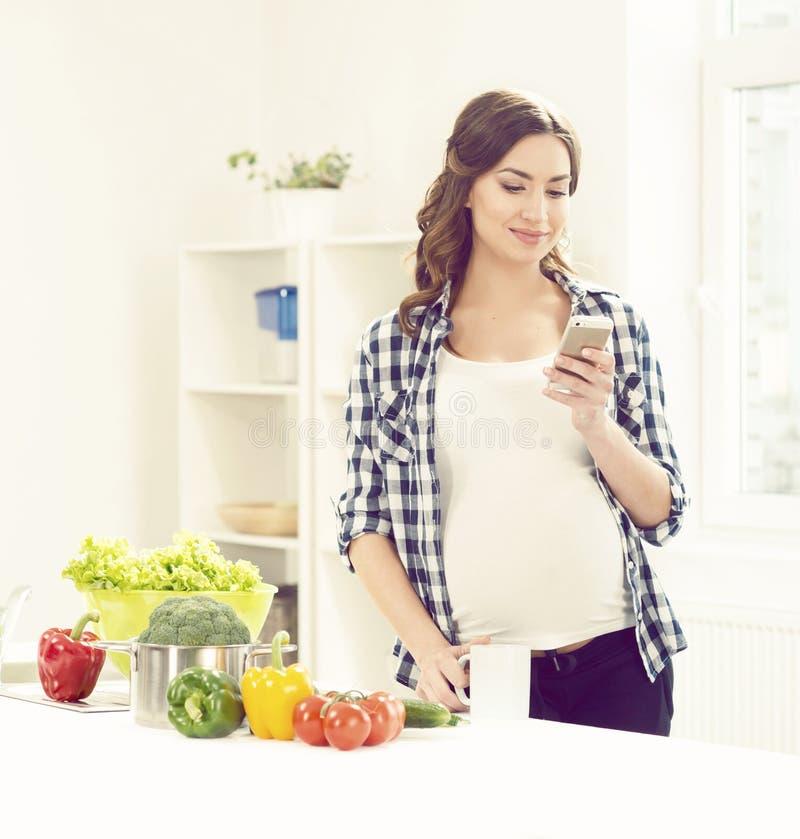 Mooie zwangere vrouw met smartphone in keuken Moederschap, stock afbeeldingen
