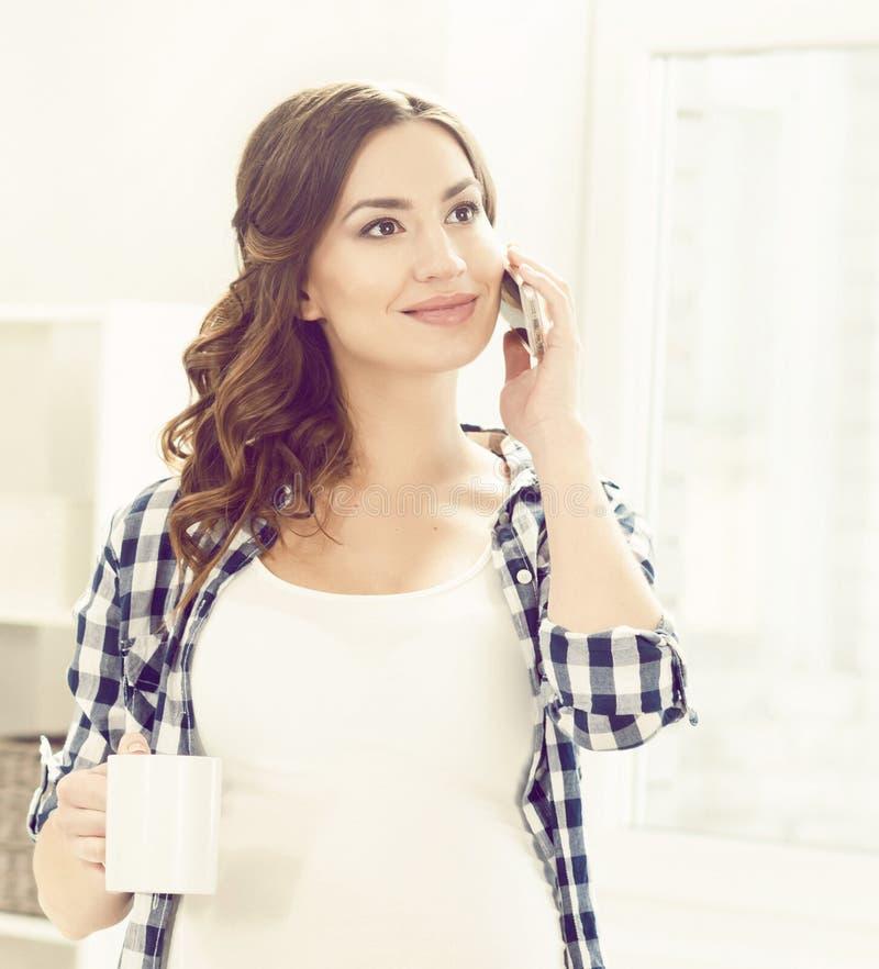 Mooie zwangere vrouw met smartphone in keuken Moederschap, royalty-vrije stock foto's
