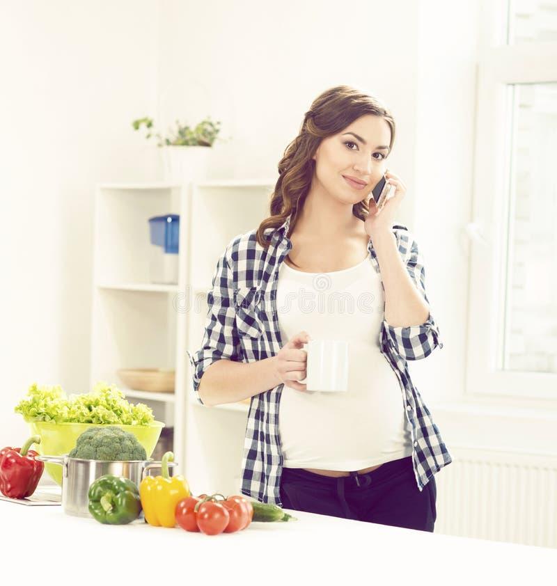 Mooie zwangere vrouw met smartphone in keuken Moederschap, royalty-vrije stock afbeelding