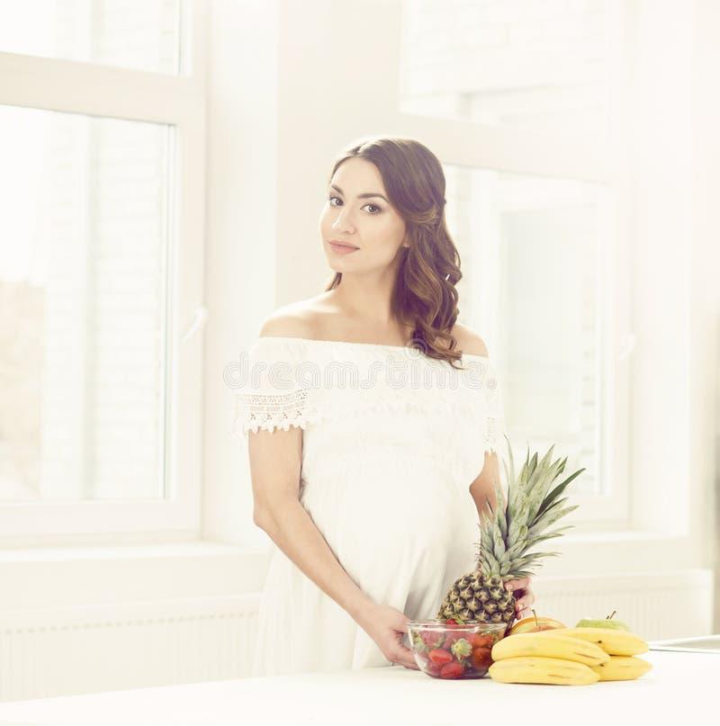 Mooie zwangere vrouw met vruchten in de keuken royalty-vrije stock foto's