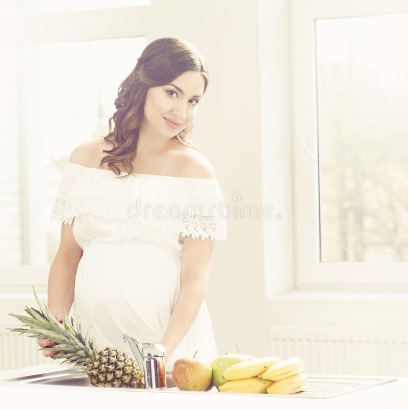 Mooie zwangere vrouw met vruchten in keuken Moederschap, pre royalty-vrije stock foto's