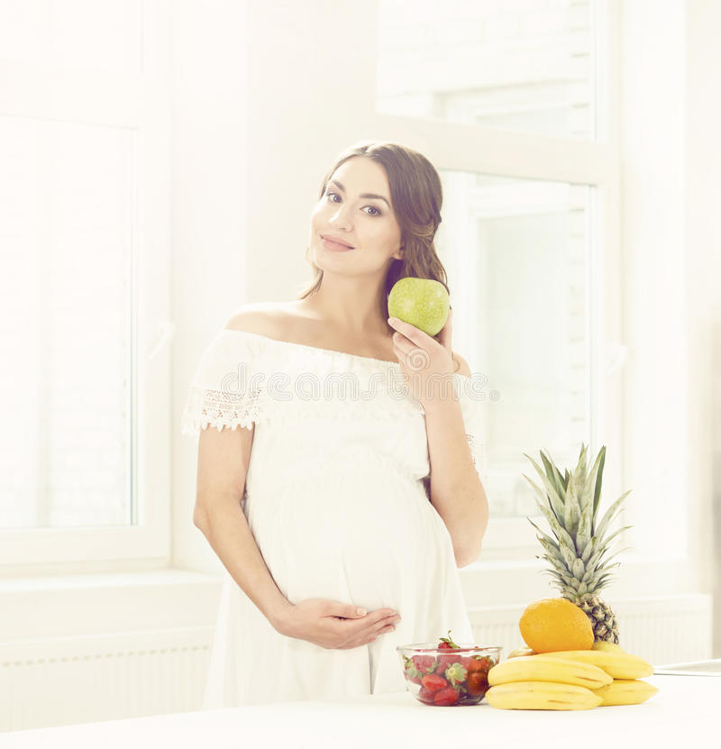 Mooie zwangere vrouw met vruchten in keuken Moederschap, pre royalty-vrije stock foto