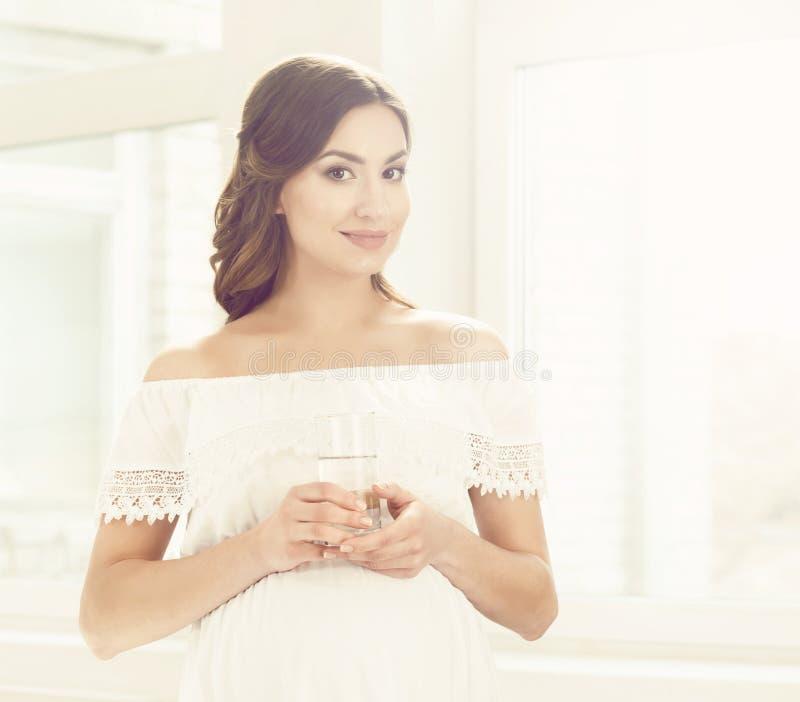 Mooie zwangere vrouw met vruchten in keuken Moederschap, pre stock foto's