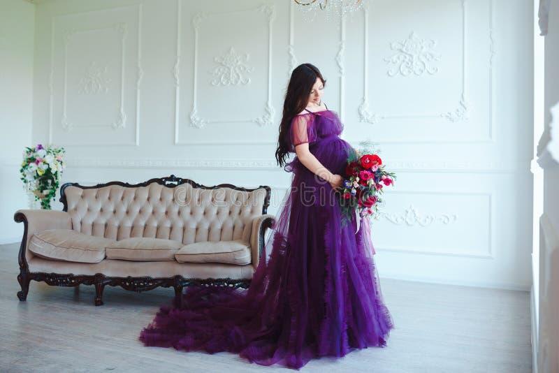 Mooie zwangere vrouw in violette tedere kleding bij luxe klassiek binnenland Manierzwangerschap stock afbeelding