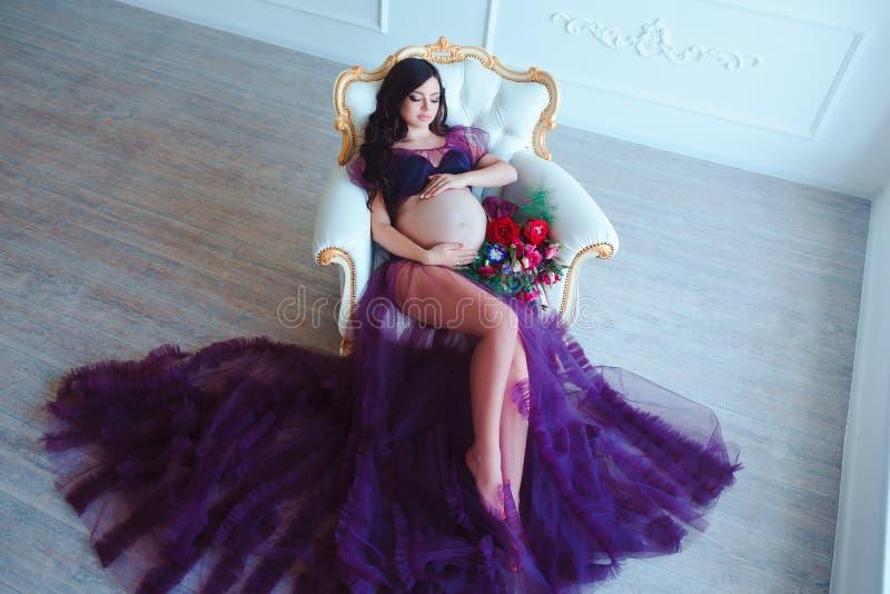 Mooie zwangere vrouw in violette tedere kleding bij luxe klassiek binnenland Manierzwangerschap stock fotografie