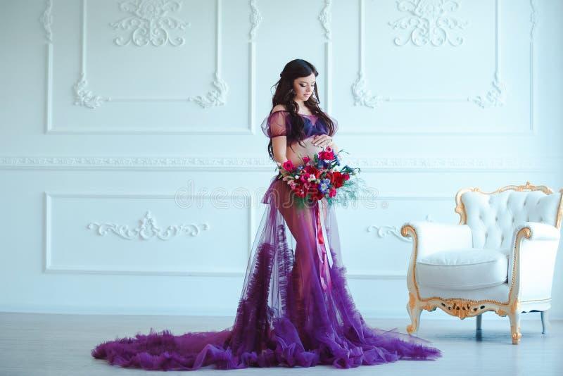 Mooie zwangere vrouw in violette tedere kleding bij luxe klassiek binnenland Manierzwangerschap stock afbeeldingen