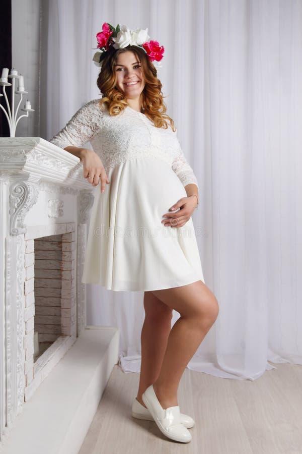 Mooie zwangere vrouw in witte kleding en kroon royalty-vrije stock fotografie
